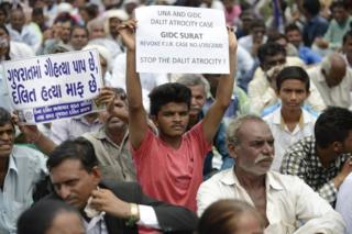 "An Indian member of the Dalit caste community holds a placard saying ""In Gujarat, Cow Slaughter is a Sin while Killing Dalits is pardonable"" (L) as he participates in a protest rally against an attack on Dalit caste members in the Gujarat town of Una, in Ahmedabad on July 31, 2016."
