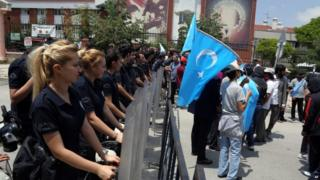 Riot police stand as a group of Uighur protesters demonstrate outside the Thai embassy in Ankara