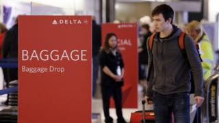 Travellers walk towards the baggage drop area for Delta airlines at Seattle-Tacoma International Airport in Washington (24 March 2015)