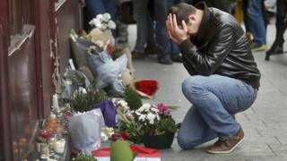 A man pays his respect outside the Le Carillon restaurant the morning after a series of deadly attacks in Paris , November 14, 2015.