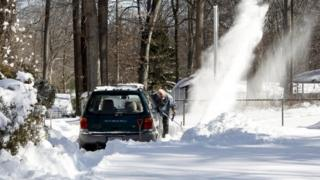 Frank Courtell clears snow with an electric snow blower on his driveway after a snowstorm inside the Washington DC