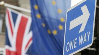 A road traffic sign is in front of the Union Jack and the European Union flag hanging outside Europe House in Smith Square, London