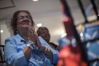 Woman praying for Hillary