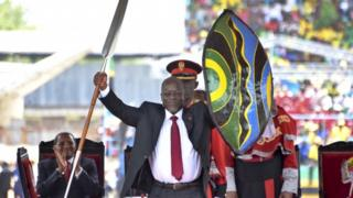 Tanzania's new President John Pombe Magufuli holds up a ceremonial spear and shield to signify the beginning of his presidency, shortly after swearing an oath during his inauguration ceremony at Uhuru Stadium in Dar es Salaam, Tanzania Thursday, Nov. 5, 2015