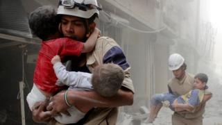 Members of the Civil Defence rescue children after what activists said was an air strike by government forces in the Shaar district of Aleppo (2 June 2014)