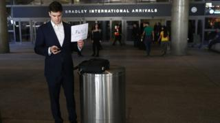 A lawyer holds a sign offering his services to those affected by President Trump's immigration order, at Los Angeles International Airport