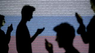 People are silhouetted (in silhouette) as they pose with mobile devices (mobiles, checking message, texting, sending texts, social media) in front of a screen projected with binary code and a Russian national flag