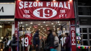 Türkiye'de indirime giren bir mağaza ve sokaktan geçenler.