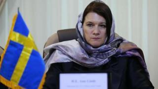 Ann Linde wearing a light purple headscarf, sitting at a desk with a small Swedish flag in Tehran, Iran