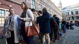 People wait in line to vote in the Dutch general e