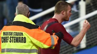 West Brom defender Chris Brunt confronts a fan after having a coin thrown at him