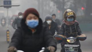 Cyclists riding through Beijing smog