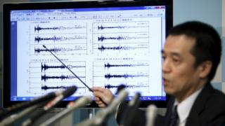 Japan Meteorological Agency's earthquake and tsunami observations division director Yohei Hasegawa points at a graph of seismic data