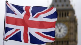 A union flag flies in front of the Palace of Westminster