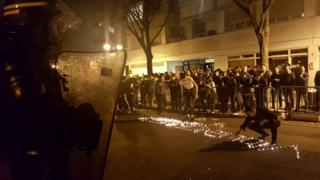 "Youths use candles to write the word ""Violence"" in the road in front of a line of riot police outside a police station in the 19th arrondissement (district) of Paris late on 27 March 2017, during clashes in the wake of the death of a Chinese national during a police intervention"