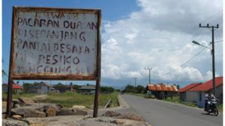 """A motorist rides past a board that, in the local language, reads """"If you date on the beach, the risk is on your own"""" in Banda Aceh"""