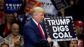 Donald Trump holds a sign supporting coal during a rally