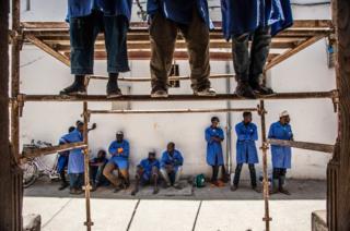 Students working on a damaged doorway Wanafunzi wakiukarabati mlango