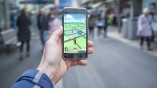 Male hand holding iPhone 6 with Pokemon Go game on a busy street