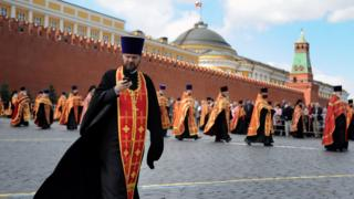 An Orthodox priest checks his mobile phone during a march in Red Square