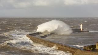 waves crashing on lighthouse