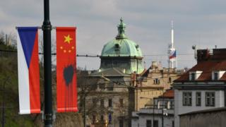 A Czech National flag hangs next to a Chinese National flag splattered with a black substance in Prague on March 26, 2016