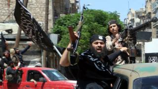 Fighters from Jabhat Fath al-Sham drive in the northern Syrian city of Aleppo while flying Islamist flags, in 2015