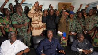 "A delegation of mutinous soldiers stand behind Ivory Coast""s defence minister Alain-Richard Donwahi (C-front) speaking to journalists after negotiations, on January 7, 2017 in Bouake."