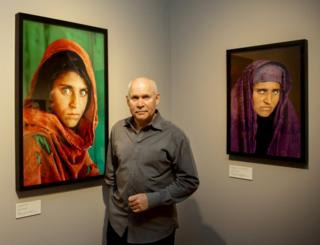"US photographer Steve McCurry poses next to his photos of the ""Afghan Girl"" Sharbat Gula in Hamburg, Germany on June 27, 2013."