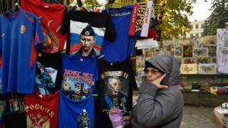 A woman sells t-shirts featuring Russian President Vladimir Putin in Chisinau on October 28, 2016