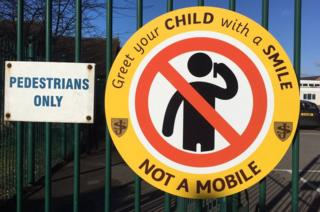 "A sign at the school gates, which says: ""Greet your child with a smile not a mobile"""