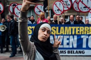 Photo of Zakia Belkhiri taking a selfie with Vlaams Belang protesters in the background