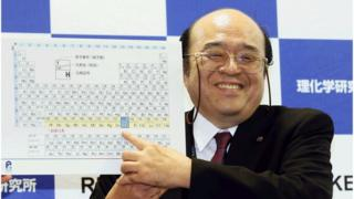 Kosuke Morita of Riken Nishina Center for Accelerator-Based Science points at periodic table of the elements.