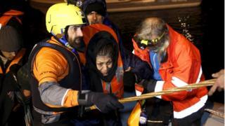 Volunteers help an Afghan refugee off a raft on Chios (28 Jan)