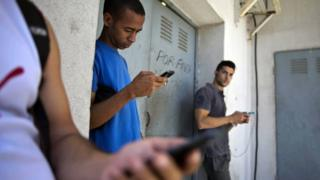 Cubans use mobile phones in Havana, 1 April 16
