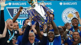 Leicester City defender Wes Morgan holds up the Premier league trophy
