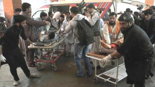 Pakistani security personnel and volunteers move victims injured in a suicide bombing to a hospital in Peshawar on 7 March 2016, after an attack on a court complex in the town of Shabqadar