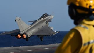 A fighter jet takes off from the Charles de Gaulle carrier