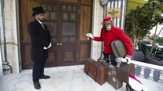 """Doorman stands at the entrance of the """"The Walled Off Hotel"""" in the West Bank city of Bethlehem, Friday, March 3, 2017."""