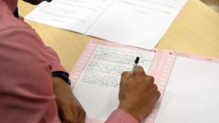 Anonymous student's hands writing an exam, file pic