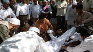 Assembled Indian Muslims bury Syed Shahabuddin, wrapped in a shroud, in New Delhi on March 4, 2017