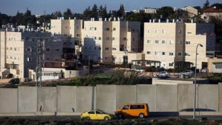 Cars drive on a road used by Palestinians from the Jalazone refugee camp past a defensive wall that surrounds the Israeli settlement of Beit El (7 April 2015)