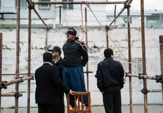 Balal, who killed Iranian youth Abdolah Hosseinzadeh in a street fight with a knife in 2007, reacts as he stands in the gallows during his execution ceremony in the northern city of Noor on April 15, 2014. Samereh Alinejad, the mother of Abdolah Hosseinzadeh spared the life of Balal, her son's convicted murderer, with an emotional slap in the face as he awaited execution prior to removing the noose around his neck.