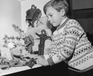 A boy examines a display of Action Man toys at the British Toy Fair in Brighton, January 1966