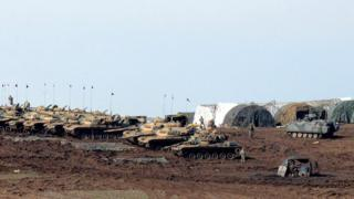 Turkish Army vehicles and tanks wait near the Syrian border in Suruc on February 23, 2015