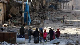 Syrians walk over rubble of damaged buildings in eastern Aleppo