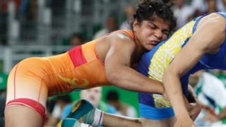 """India's Sakshi Malik (red) wrestles with Kirghyzstan""""s Aisuluu Tynybekova"""