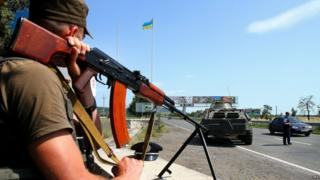 A Ukrainian serviceman guards the road at the border of the western city of Uzhhorod