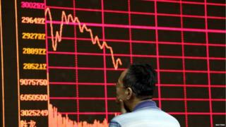 An investor looks at an electronic board showing stock information of Shanghai Stock Exchange Composite Index at a brokerage house in Beijing, August 26, 2015