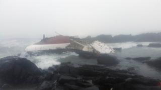 The capsized yacht washed up on rocks on South Africa's west coast